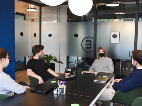 people with masks seeting in the meeting room at the table