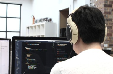 developer with headphones coding at computer